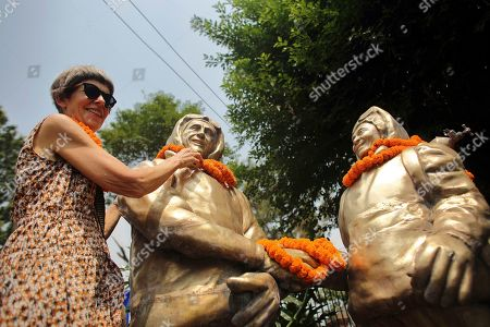 New Zealand mountaineer Edmund Hillary's daughter, Sarah Hillary garlands statues of Hillary and Tenzing Norgay Sherpa, right, the first climbers to ascent Mount Everest during a ceremony to mark the anniversary of the first ascent in Kathmandu, Nepal, . Nepal has commemorated the anniversary of the first ascent of Mount Everest amid a climbing season marred by the highest death toll in four years and a debate on whether the government should limit permits to prevent dangerous overcrowding on the world's highest peak