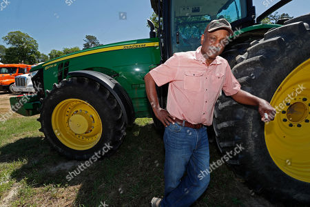 Stock Picture of Larry Walls, a farmer and businessman in Louise, Miss., stands along side one of his two John Deere tractors that are sitting unused due to backwater flooding in the Mississippi Delta