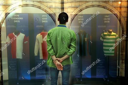 A visitor looks at soccer jerseys on display during the opening of the Champions Legends Gallery at the House of the Post Office in Madrid, Spain, 29 May 2019. The exhibition features original jerseys of 22 UEFA Champions League winning teams as well as nine jerseys that belonged to soccer legends like Alfredo Di Stefano, Johan Cruyff, Diego Maradona, Zinedine Zidane, Lionel Messi, and Cristiano Ronaldo. The event will be open to the public from 30 May to 02 June 2019 on the occasion of the UEFA Champions League final between Tottenham Hotspur and Liverpool FC at the Wanda Metropolitano stadium in Madrid, Spain, on 01 June 2019.