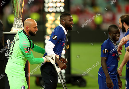 Goalkeeper Wilfredo Caballero of Chelsea helps Antonio Rudiger on his crutches