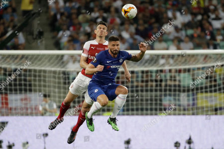 Chelsea's Olivier Giroud, foreground, and Arsenal's Laurent Koscielny jump for the ball during the Europa League Final soccer match between Arsenal and Chelsea at the Olympic stadium in Baku, Azerbaijan