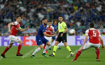 Referee Gianluca Rocchi watches as Chelsea's Olivier Giroud, center, runs after the ball between Arsenal's Laurent Koscielny, left, and Arsenal's Sokratis Papastathopoulos, right, during the Europa League Final soccer match between Chelsea and Arsenal at the Olympic stadium in Baku, Azerbaijan