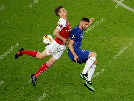 Arsenal's Laurent Koscielny, left, and Chelsea's Olivier Giroud battle for the ball during the Europa League Final soccer match between Chelsea and Arsenal at the Olympic stadium in Baku, Azerbaijan