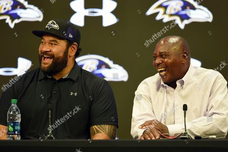 Former Baltimore Ravens NFL football player Haloti Ngata, left, and former general manager Ozzie Newsome laugh during a news conference announcing Ngata's retirement from the NFL, in Owings Mills, Md