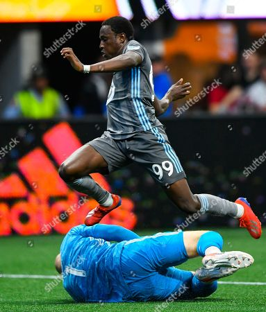 Atlanta United goalkeeper Brad Guzan makes a save as Minnesota United forward Abu Danladi (99) leaps over him after a shot during the first half of an MLS soccer match, in Atlanta