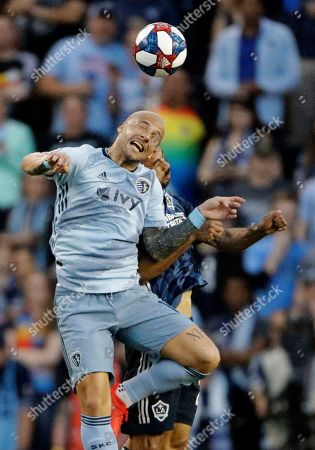 Sporting Kansas City midfielder Yohan Croizet, front, beats LA Galaxy defender Giancarlo Gonzalez to the ball during the first half of an MLS soccer match, in Kansas City, Kan