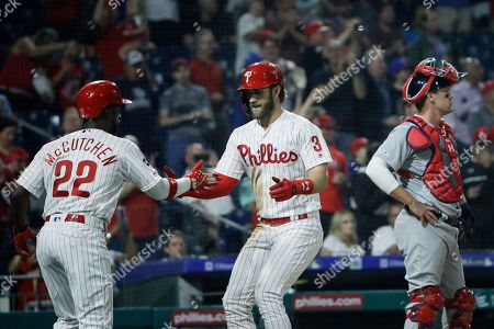 Philadelphia Phillies' Bryce Harper meets with Andrew McCutchen after hitting a home run off of St. Louis Cardinals starting pitcher Genesis Cabrera during the third inning of a baseball game, in Philadelphia