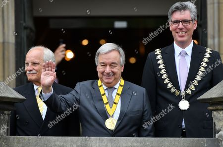 Stock Photo of United Nations (UN) Secretary-General Antonio Guterres (C) waves from a balcony after receiving the Charlemagne medal from the Mayor of Aachen Marcel Philipp (R) and German politician Juergen Linden (L) during the Charlemagne Prize (Karlspreis) ceremony at the town hall in Aachen, Germany, 30 May 2019. The International Charlemagne Prize of the German City of Aachen is awarded annually since 1950 to people who have contributed to the ideals upon which Europe has been founded.