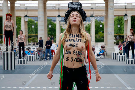 "Femen activist Inna Shevchenko and other women with messages painted on their naked chests gesture during a protest against women murdered in France, at the Palais Royal in Paris, . Some sixty women activists of the Femen stage a protest to ""pay attention"" to some 60 women ""murdered"" by men since the beginning of the year and denounce ""indifference from the state."" Writing on Shevchenko's body reads; '""Celine, thrown from a window with her 3 month baby"