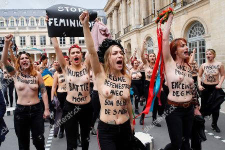 "Femen activist Inna Shevchenko, center, and other women with messages painted on their naked chests gesture during a protest against women murdered in France at the Palais Royal in Paris, . Some sixty women activists of the Femen stage a protest to ""pay attention"" to some 60 women ""murdered"" by men since the beginning of the year and denounce ""indifference from the state"