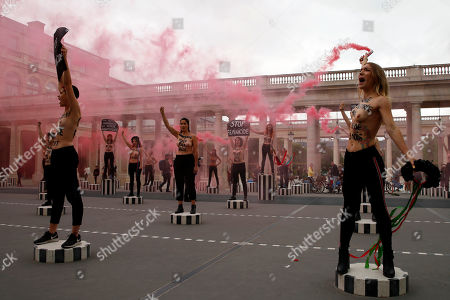 "Femen activist Inna Shevchenko, center, and other women with messages painted on their naked chests gesture with flares during a protest against women murdered in France at the Palais Royal in Paris, . Some sixty women activists of the Femen stage a protest to ""pay attention"" to some 60 women ""murdered"" by men since the beginning of the year and denounce ""indifference from the state"