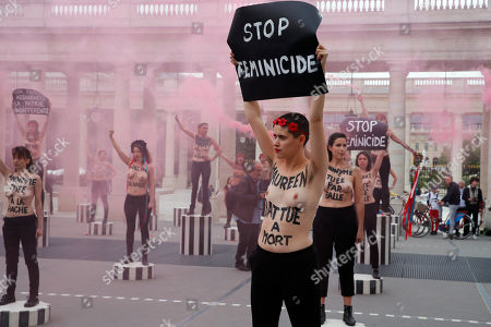 "Femen activist Inna Shevchenko, center, and other women with messages painted on their naked chests gesture with flares during a protest against women murder at the Palais Royal in Paris, . Some sixty women activists of the Femen stage a protest to ""pay attention"" to some 60 women ""murdered"" by men since the beginning of the year and denounce ""indifference from the state"