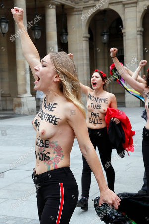 "Femen activist Inna Shevchenko, left, and other women with messages painted on their naked chests gesture during a protest against women murder at the Palais Royal in Paris, . Some sixty women activists of the Femen stage a protest to ""pay attention"" to some 60 women ""murdered"" by men since the beginning of the year and denounce ""indifference from the state"