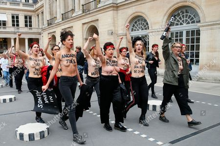"Femen activist Inna Shevchenko, second right, and other women with messages painted on their naked chests gesture during a protest against women murder at the Palais Royal in Paris, . Some sixty women activists of the Femen stage a protest to ""pay attention"" to some 60 women ""murdered"" by men since the beginning of the year and denounce ""indifference from the state"