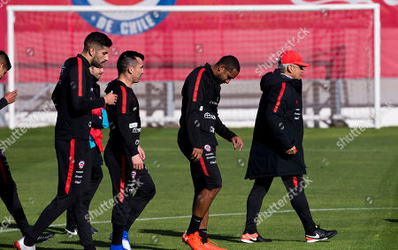 Chile's Guillermo Maripan, from left, Gary Medel, Jean Beausejour and coach Reinaldo Rueda, walk on pitch during a training session, in Santiago, Chile, ahead of the Copa America in neighboring Brazil