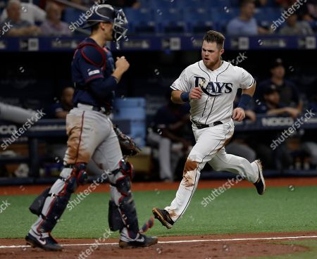 Stock Image of Tampa Bay Rays' Christian Arroyo, right, scores in front of Minnesota Twins catcher Jason Castro on a two-run single by Brandon Lowe off starting pitcher Martin Perez during the third inning of a baseball game, in St. Petersburg, Fla