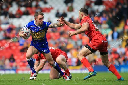 Richie Myler of Leeds Rhinos hands off Ryan Morgan of London Broncos