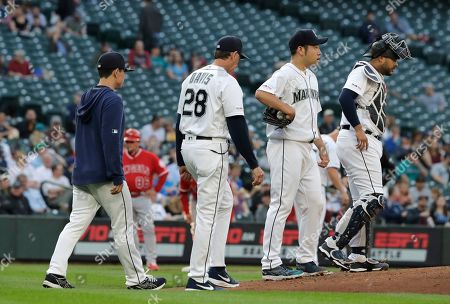 Seattle Mariners starting pitcher Yusei Kikuchi, second from right, walks to the mound with catcher Omar Narvaez, right, pitching coach Paul Davis (28) and a translator, left, for a mound conference during the second inning of the team's baseball game against the Los Angeles Angels, in Seattle