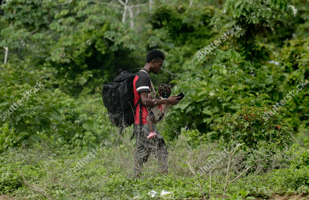 A migrant carrying a girl walks near the Tuquesa river, in Bajo Chiquito, Darien province, Panama. Panamanian President Juan Carlos Varela said last week that at least 4,000 migrants were in Bajo Chiquito, Penitas and in western Panama near Costa Rica, the next stop on the road north to the United States