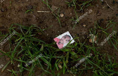 The mugshot of an unknown migrant lays on the ground in Bajo Chiquito, Darien province, Panama. As migrants surge on the country's borders, Panamanian President Juan Carlos Varela acknowledged the difficulty of dealing with problem, which has left authorities scrambling to impose order