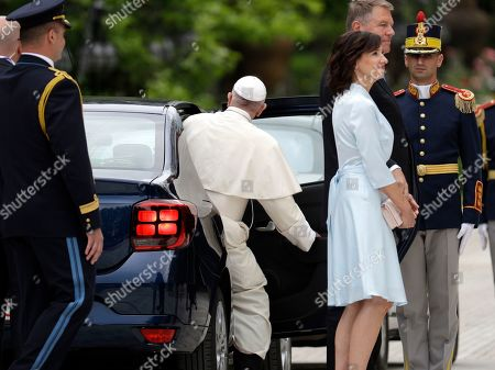 Pope Francis gets into a car behind Romanian President Klaus Iohannis and his wife Carmen during a welcome ceremony at the Cotroceni Presidential Palace, in Bucharest, Romania, . Francis arrived in Romania on Friday for a three-day, cross-country pilgrimage that in many ways is completing the 1999 trip by St. John Paul II that marked the first-ever papal visit to a majority Orthodox country