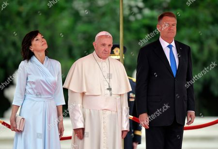 Pope Francis stands with Romanian President Klaus Iohannis, right, and his wife Carmen during a welcome ceremony in the gardens of the Cotroceni Presidential Palace, in Bucharest, Romania, . Francis arrived in Romania on Friday for a three-day, cross-country pilgrimage that in many ways is completing the 1999 trip by St. John Paul II that marked the first-ever papal visit to a majority Orthodox country