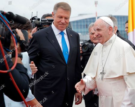 Pope Francis is introduced by Romanian President Klaus Iohannis, center, to his wife Carmen, left, upon the pontiff's arrival from Rome at Henri Coanda International Airport in Otopeni, near Bucharest, Romania, . Pope Francis is heading to Romania for a three-day, cross-country pilgrimage that in many ways is completing the 1999 trip by St. John Paul II that marked the first-ever papal visit to a majority Orthodox country