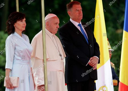 Pope Francis stands with Romanian President Klaus Iohannis, right, and his wife Carmen during a welcome ceremony at the Cotroceni Presidential Palace, in Bucharest, Romania, . Francis arrived in Romania on Friday for a three-day, cross-country pilgrimage that in many ways is completing the 1999 trip by St. John Paul II that marked the first-ever papal visit to a majority Orthodox country