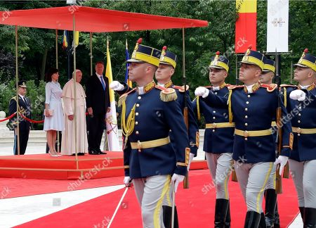 Pope Francis, Romanian President Klaus Iohannis, and his wife Carmen, left, review the honor guard during a welcome ceremony at the Cotroceni Presidential Palace, in Bucharest, Romania, . Francis arrived in Romania on Friday for a three-day, cross-country pilgrimage that in many ways is completing the 1999 trip by St. John Paul II that marked the first-ever papal visit to a majority Orthodox country