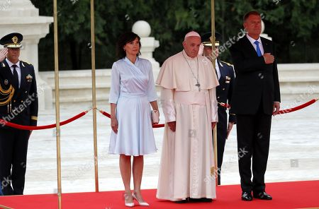 Pope Francis (C), accompanied by Romania's President Klaus Iohannis (R) and his wife Carmen Iohannis (L) review the honor guard at Cotroceni Presidential Palace in Bucharest, Romania 31 May 2019. Pope Francis is on a three-day visit to Romania from 31 May to 02 June 2019. The pontiff visit takes place 20 years after Pope St. John Paul II's historic visit to Romania, having the motto 'Let's Walk Together'.