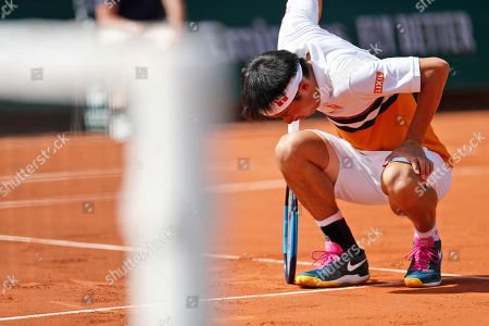 Japan's Kei Nishikori leans on his racket after missing a shot against Serbia's Laslo Djere during their third round match of the French Open tennis tournament at the Roland Garros stadium in Paris
