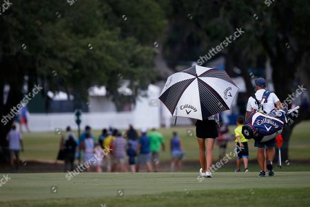 Jenny Haglund of Sweden, walks off the course with caddie Casey Johnson due to inclement weather during the second round of the U.S. Women's Open golf tournament, in Charleston, S.C