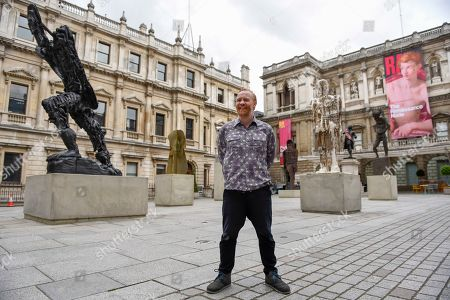 Celebrated artist Thomas Houseago poses alongside his major installation of six recent sculptures in the courtyard of the Royal Academy of Arts