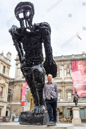 Stock Image of Celebrated artist Thomas Houseago poses alongside his major installation of six recent sculptures in the courtyard of the Royal Academy of Arts