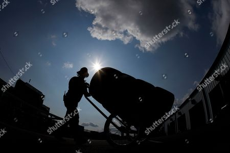 Stock Image of A crew member with the car of Corey LaJoie pushes a stack of tires to their garage stall during a practice session for Sunday's NASCAR Cup Series auto race at Pocono Raceway, in Long Pond, Pa