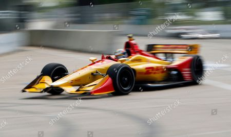 In this image taken with a slow shutter speed, Ryan Hunter-Reay rounds the seventh turn during practice for the first race of the IndyCar Detroit Grand Prix auto racing doubleheader, in Detroit