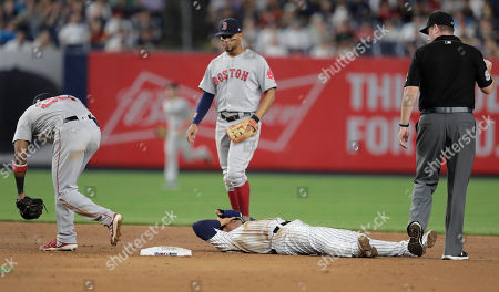New York Yankees' Gleyber Torres is slow to get up after being tagged out trying to steal second by Boston Red Sox second baseman Eduardo Nunez, left, to end the eighth inning of a baseball game, in New York. Also seen are Red Sox shortstop Xander Bogaerts, center, and second base umpire Chris Conroy. The Yankees won 4-1