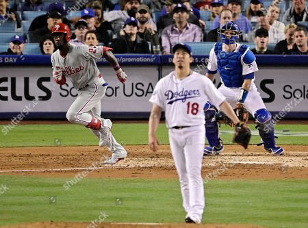 Philadelphia Phillies' Andrew McCutchen, left, runs to first as he hits a solo home run while Los Angeles Dodgers starting pitcher Kenta Maeda, center, of Japan, watches along with catcher Will Smith during the fourth inning of a baseball game, in Los Angeles