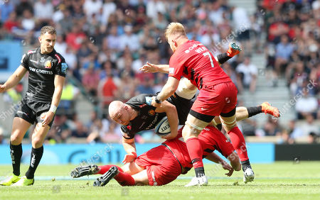 Stock Photo of Matt Kvesic of Exeter Chiefs is upended by Jamie George of Saracens - with Jackson Wray of Saracens