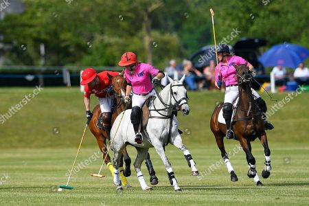 Hector Fair of Hackett Army plays a shot watched by Heloise Wilson-Smith and Jessica Andrews of Women in Polo during Heroes Polo Day at Tidworth Polo Club on 1st June 2019