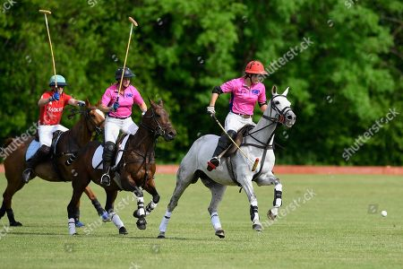 Heloise Wilson-Smith of Women in Polo charges upfield supported by Jessica Andrews during Heroes Polo Day at Tidworth Polo Club on 1st June 2019