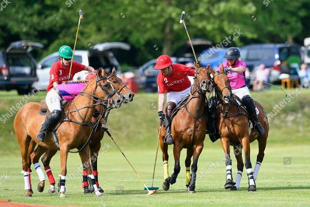 Hector Fair of Hackett Army plays a shot under pressure from Heloise Wilson-Smith left and Jessica Andrews of Women in Polo during Heroes Polo Day at Tidworth Polo Club on 1st June 2019