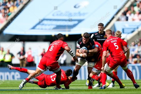 Dave Ewers of Exeter Chiefs is tackled by Alex Lozowski and Brad Barritt of Saracens
