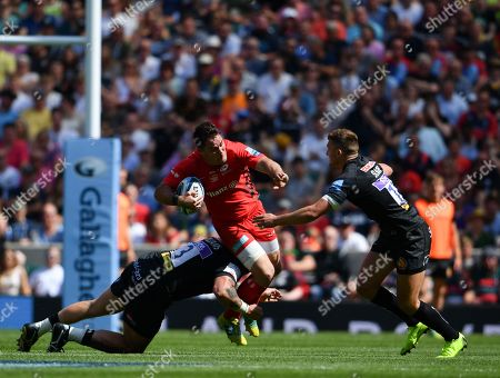 Saracens' Brad Barritt is tackled by Exeter Chiefs' Harry Williams (left) and Henry Slade