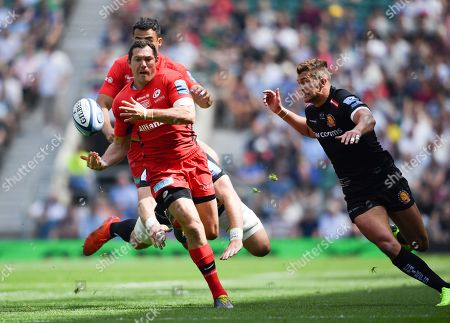Alex Goode of Saracens passes over his shoulder to Alex Lozowski as Henry Slade of Exeter closes in