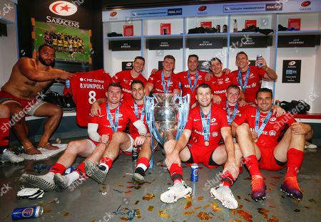 Saracens backs with the Trophy whilst Billy Vunipola gets into the picture. Backrow (l-r) David Strettle, Owen Farrell, Brad Barritt, Alex Goode and Liam Williams. Front row (l-r) Ben Spencer, Sean Maitland, Richard Wigglesworth, Nick Tompkins and Alex Lozowski