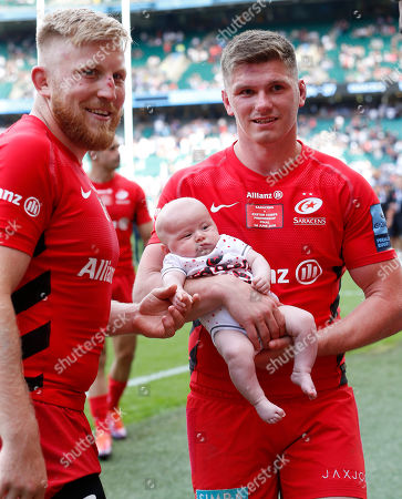 Stock Picture of Owen Farrell (right) of Saracens holds his son Tommy whilst talking with teammate Jackson Wray