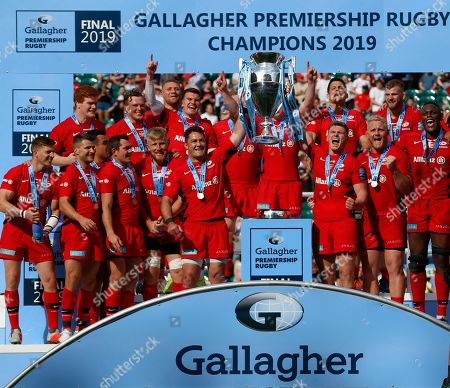 Brad Barritt and Owen Farrell lifs the Premiership Trophy surrounded by teammates after the game