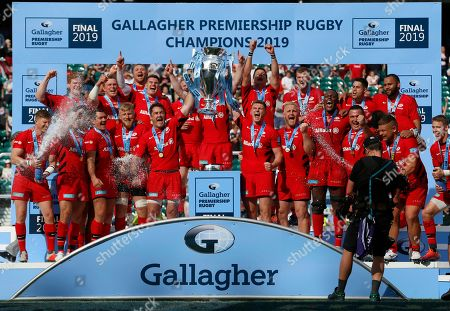 Brad Barritt and Owen Farrell lifts the Premiership Trophy surrounded by teammates after the game
