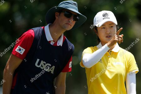 Yan Liu of China, speaks with her caddie Axel Bettan before hitting off the first tee during the third round of the U.S. Women's Open golf tournament, in Charleston, S.C